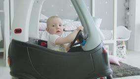 Прелестная девушка малыша управляя малолитражным автомобилем игрушки дома сток-видео