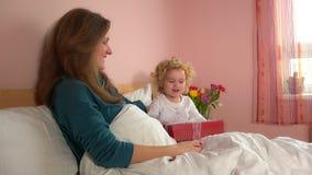 Прелестная девушка ребенка приносит присутствующую подарочную коробку к ее матери в пижамах видеоматериал