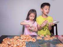 Прелестная девушка ребенк и упаковка мальчика отдельная испекли сосиску свинины Стоковое Фото