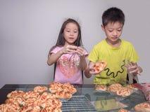Прелестная девушка ребенк и упаковка мальчика отдельная испекли сосиску свинины Стоковые Фото