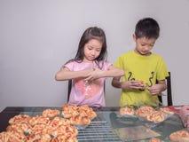 Прелестная девушка ребенк и упаковка мальчика отдельная испекли сосиску свинины Стоковое Изображение RF