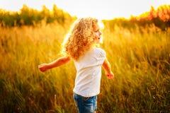 Прелестная девушка с вьющиеся волосы на заходе солнца стоковое фото