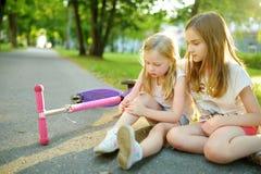 Прелестная девушка утешая ее маленькую сестру после того как она упала с ее самоката на парке лета Ребенок получая повреждение по стоковое изображение rf