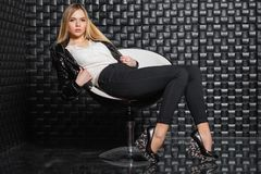 Прелестная женщина представляя на стуле стоковое фото