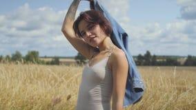 Прелестная женщина с bodysuit коротких волос нося держа куртку джинсов на ее руках стоя на пшеничном поле Уверенный акции видеоматериалы