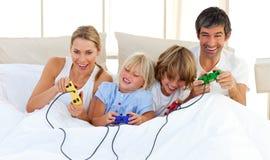 прелестная игра семьи спальни играя видео Стоковая Фотография RF