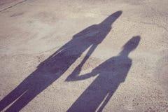 Прелестная концепция семьи: Тень по причине женщины и детей стоя на конкретном поле и держа руку совместно стоковое фото rf