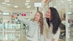 Прелестная курчавая с волосами маленькая девочка наслаждаясь ходить по магазинам на торговом центре с ее матерью сток-видео