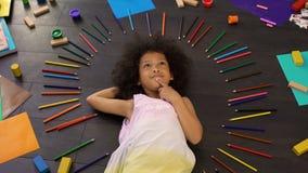 Прелестная маленькая Афро-американская девушка лежа на поле и думая о праздниках стоковое фото