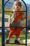 Прелестная маленькая девочка взбираясь вверх на лестницах на спортивной площадке Стоковое Изображение RF