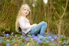 Прелестная маленькая девочка выбирая первые цветки весны в древесинах на красивый солнечный весенний день стоковое изображение rf