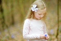 Прелестная маленькая девочка выбирая первые цветки весны в древесинах на красивый солнечный весенний день стоковое фото rf