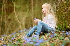 Прелестная маленькая девочка выбирая первые цветки весны в древесинах на красивый солнечный весенний день стоковая фотография