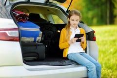 Прелестная маленькая девочка готовая для того чтобы пойти на каникулы с ее родителями Оягнитесь сидеть в багажнике автомобиля и ч стоковые фото