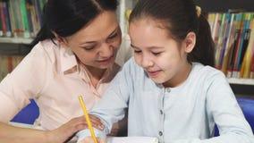 Прелестная маленькая девочка делая домашнюю работу с ее матерью стоковые изображения