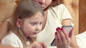 Прелестная маленькая девочка используя умный телефон с ее матерью видеоматериал