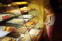 Прелестная маленькая девочка смотря свежие испеченные печенья на дисплее в небольшом магазине в Вильнюсе, Литве Ребенок выбирая д стоковая фотография rf