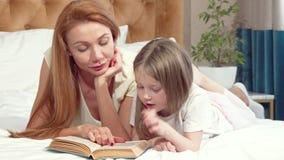 Прелестная маленькая девочка уча чтение дома с ее матерью видеоматериал