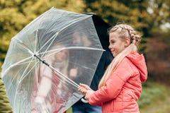 прелестная маленькая дочь держа зонтик пока родители стоковая фотография rf