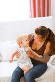 прелестная мама кресла младенца играя детенышей Стоковое Изображение