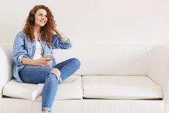 Прелестная мечтательная молодая женщина носит модные одежды, слушает аудио или музыка в наушниках соединенных к мобильному телефо Стоковое Изображение