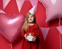 Прелестная милая девушка с розовыми воздушными шарами и подарком красного цвета присутствующими и крышкой дня рождения Стоковые Изображения RF
