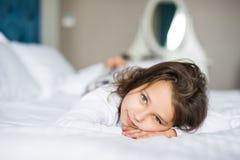 Прелестная милая усмехаясь маленькая девочка проспала вверх в ее кровати стоковая фотография