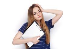 Прелестная свежая смотря белокурая женщина в голубой футболке держа папку зажима Идея дела и концепция эмоции Стоковая Фотография RF