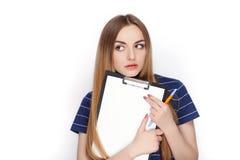 Прелестная свежая смотря белокурая женщина в голубой футболке держа папку зажима Идея дела и концепция эмоции Стоковое Изображение