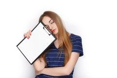 Прелестная свежая смотря белокурая женщина в голубой футболке держа папку зажима Идея дела и концепция эмоции Стоковые Изображения RF