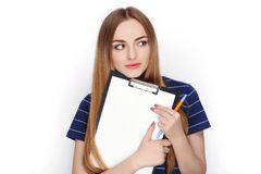 Прелестная свежая смотря белокурая женщина в голубой футболке держа папку зажима Идея дела и концепция эмоции Стоковая Фотография