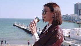 Прелестная стильная девушка брюнета идя набережной около моря и есть мороженое на солнечном дне акции видеоматериалы