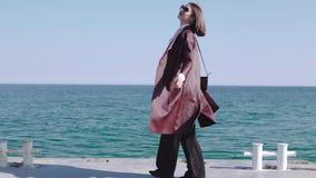 Прелестная стильная девушка брюнета идя набережной около моря и закручивая вокруг на солнечный день сток-видео