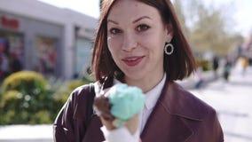 Прелестная стильная девушка брюнета идя broadwalk и есть мороженое на солнечном дне акции видеоматериалы