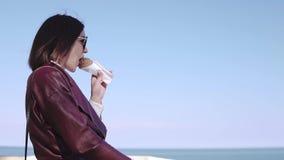 Прелестная стильная девушка брюнета идя broadwalk и есть мороженое на солнечном дне видеоматериал