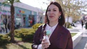 Прелестная стильная девушка брюнета идя broadwalk и есть мороженое на солнечном дне сток-видео