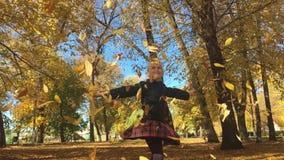Прелестная счастливая девушка школы бросая упаденные листья вверх, играющ в девушке леса осени красивой имея потеху внутри видеоматериал