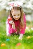 Прелестное звероловство маленькой девочки для пасхального яйца в зацветая саде весны на день пасхи Стоковое фото RF