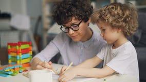 Прелестное изображение чертежа ребенка с карандашами пока мать говоря и усмехаясь сток-видео