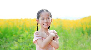 Прелестное маленькое азиатское чувство девушки ребенка свободное с крестом сложенным рукой one рука в поле Sunhemp с солнечным св стоковое изображение