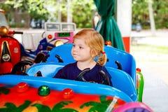 Прелестное маленькое катание девушки малыша на смешном автомобиле на carousel карусели в парке атракционов Счастливый здоровый ре стоковая фотография rf