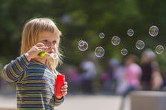 прелестное мыло пузырей дуновения младенца Стоковые Изображения RF