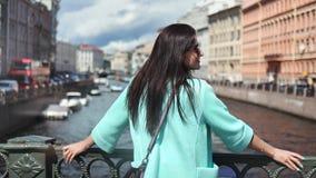 Прелестное положение женщины перемещения брюнета на мосте восхищая изумляя городской пейзаж реки наслаждаясь праздником сток-видео