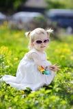 прелестное усаживание девушки поля одуванчика Стоковые Изображения