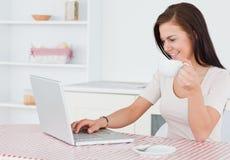 Прелестно женщина используя ее компьтер-книжку и имеющ чай Стоковая Фотография