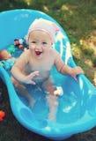 Прелестно младенец имея ванну в саде Стоковые Фото