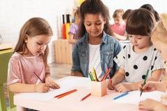 Прелестные дети рисуя совместно на таблице Деятельности при playtime детского сада стоковые изображения rf