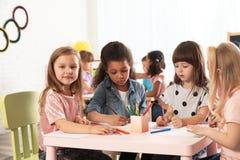 Прелестные дети рисуя совместно на таблице Деятельности при playtime детского сада стоковая фотография
