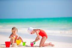 Прелестные маленькие девочки во время летних каникулов Дети играя с пляжем забавляются на белом пляже Стоковое фото RF