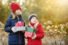 Прелестные маленькие девочки держа кучу подарков рождества на красивый солнечный зимний день стоковые изображения